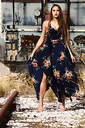 Houston fashion model Rachael Campbell posing in long sun dress on train tracks in front of abandoned train engine by Gerard Harrison, Image Theory Photoworks