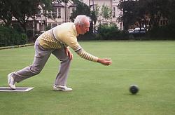Elderly man playing game of bowls,