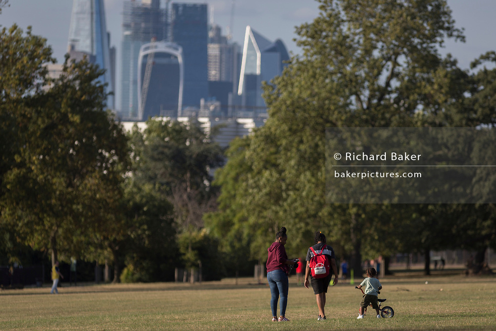 A family walk through Ruskin Park with the skyline of the City of London's financial district, on 8th August 2018, in London, England.