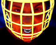 Screaming man wearing a glowing face guard.Black light