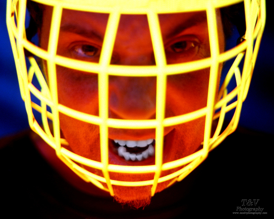 Screaming man wearing a glowing face guard.Black light