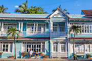 A couple of men sit outside a freshly painted old colonial style wood frame hotel at sunrise along the main road in Cabarete, the Dominican Republic.