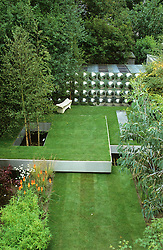Overhead view showing three 'floating' steel trays creating different levels of lawn. Betula utilis var. jacquemontii ( silver birch ) growing up through 'hole' in lawn. Workshop at rear of garden clad with aluminium disks. Design Diarmuid Gavin