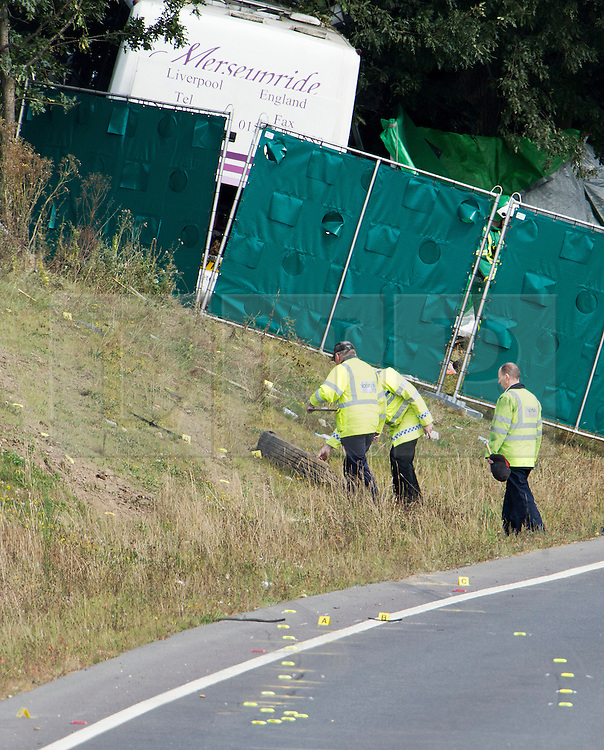 © London News Pictures. 11/09/2012. Hindhead, UK . A police officers examining a tyre on the roadside at the scene of a fatal bus crash on the north bound A3 motorway near Hindhead Tunnel, Hindhead, Surrey on September 11, 2012.Three people were killed and a number of others seriously injured when a coach carrying overturned after crashing into a tree. Photo credit: Ben Cawthra/LNP