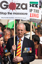 London, August 23rd 2014. A man wearing military medals protests alongside hundreds demonstrating outside Downing Street, demanding that Britain stops arming Israel.