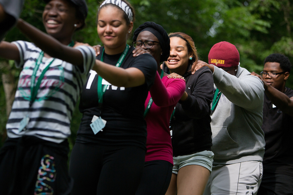 "Participants in Ohio University's Junior Executive Business Program close their eyes and lead each other on a ""sherpa walk"" during the Ropes Challenge Course on July 13, 2014. Photo by Lauren Pond"