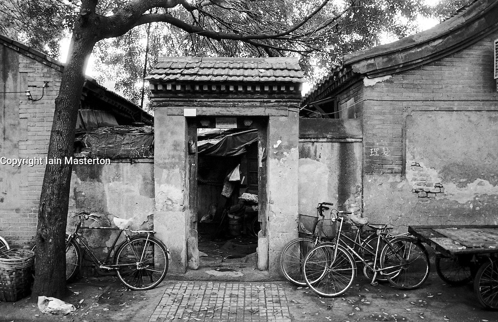 Bicycles parked at doorway to traditional courtyard house in an old Beijing hutong or alleyway