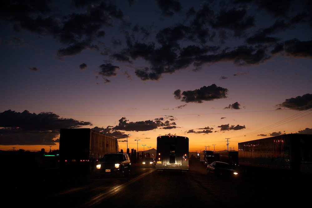 Mexico/US Border trip - Agua Perieta/ Douglas Arizona. United World College students study Migrant and immigration issues  Traffic- cars trucks and busses- drive under a glowing sunset in Agua Perieta, Mexico.