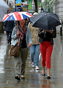 © Licensed to London News Pictures. 18/07/2012. London, UK People with umbrellas walk along Whitehall. Rain in Central London today 18th July. Photo credit : Stephen Simpson/LNP