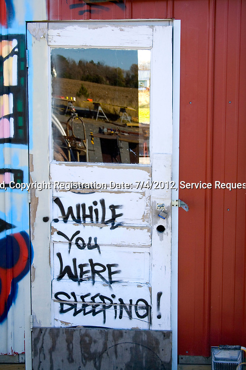 "Door to workshop with ""while you were sleeping"" quote on the outside. Franconia Sculpture Park Franconia Minnesota MN USA"