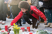 Brussels 23 March 2016. People from Brussels gathered at the Beurs square in the center of town to remember the victims of the terrorist attacks at Zaventem and Maalbeek underground station.boy lighting candles