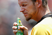 ST. LOUIS, MO - JUNE 30: A.J. Burnett #34 of the Pittsburgh Pirates sprays sunscreen on his face during the game against the St. Louis Cardinals at Busch Stadium on June 30, 2012 in St. Louis, Missouri. The Pirates won 7-3 as temperatures reached 103 degrees during the game. (Photo by Joe Robbins)