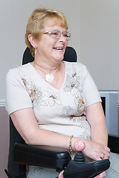 Female wheelchair user at home laughing,