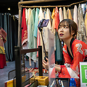 Nai Nai, a 23-year-old live-streamer in Shanghai, China, looks at her camera during a visit to a traditional Chinese dress shop.