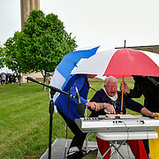 During a sudden downpour during the National Day of Prayer ceremony, Bonnie Hanchett, center, tried to cover her keyboard with plastic while being protected with umbrellas by Joyce McHenry, left, and trumpet player Jim Anderson, right, on the southeast side of the Liberty Memorial grounds. Attendees at far left moved inside the National World War I Museum for the continuation of the prayer celebration.