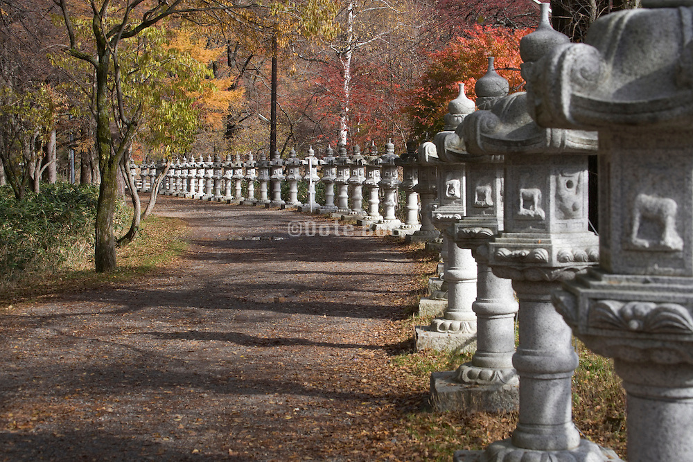 a rural road lined with stone toro lanterns Japan