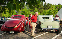 Dave and Katie Ewing check out a 1940 red Ford Coupe and a 1942 Green Ford Bobber during Cruise Night at the Gilford Community Center on Thursday evening.   (Karen Bobotas/for the Laconia Daily Sun)