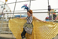 Brooklyn, New York, USA. 10th August 2013. Stilt walker KAE BURKE, of Lady Circus, wears a fancy dress and gold cape costume, as she walks high on stilts during the 3rd Annual Coney Island History Day celebration. The Wonder Wheel is seen at left behind her.