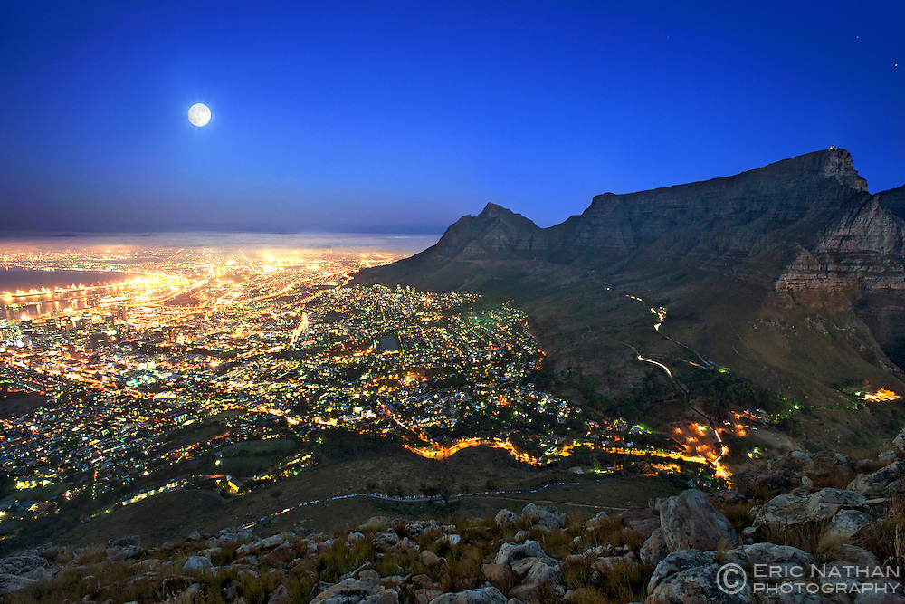 View of the full moon rising over the city of Cape Town with Table Mountain on the right.