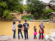 16 JUNE 2015 - SUNGAI KOLOK, THAILAND:  People wait on the Thai side of the Kolok River to go to Malaysia. The border between Thailand and Malaysia in Sungai Kolok, Narathiwat, Thailand. Thai and Malaysians cross the border freely for shopping and family visits. The border here is the Kolok River (Sungai is the Malay word for river).        PHOTO BY JACK KURTZ