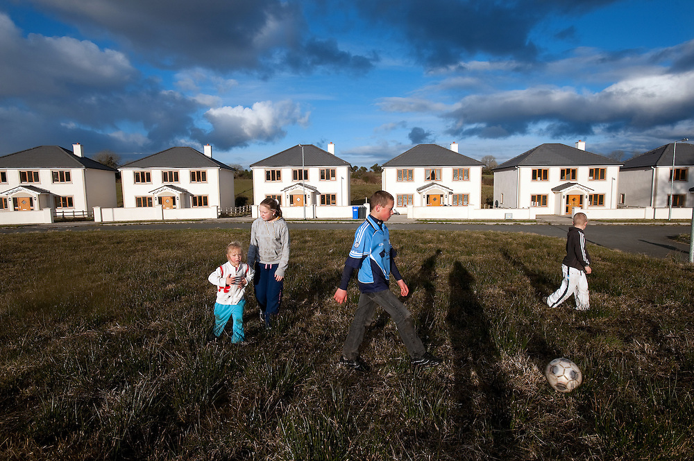 The Ozdobinski family playing in a field in front of their house, the one with curtains, in Drumshanbo, Co. Leitrim. Of the twelve exclusive detached houses in the development, only two are occupied.