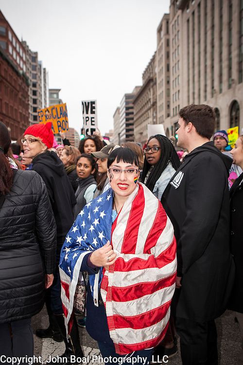 "Alicia Zen, traveled from New York City, with the flag of ""Mr. Hartstein"" a Vietnam Veteran who recently died from cancer to participate in the Women's March on Washington where an anticipated 200,000 people turned into an estimated 500,000 to 1 million people, on Saturday, January 21, 2017.  When asked about her hopes for the next 4 years, Zen said she hopes, ""...we still move forward with progress...that we become more equal, tolerant and accepting of each other...""  John Boal Photography"