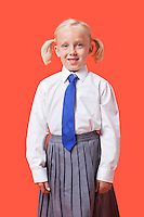 Portrait of a happy young girl in school uniform over orange background