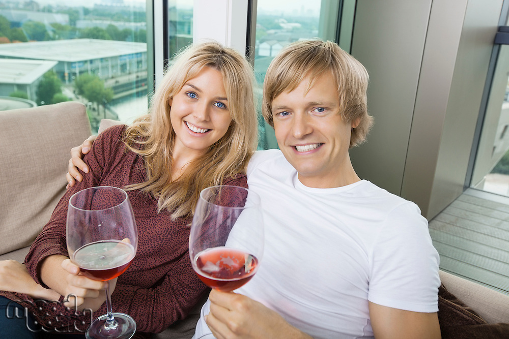Portrait of happy couple with wine glasses in living room at home