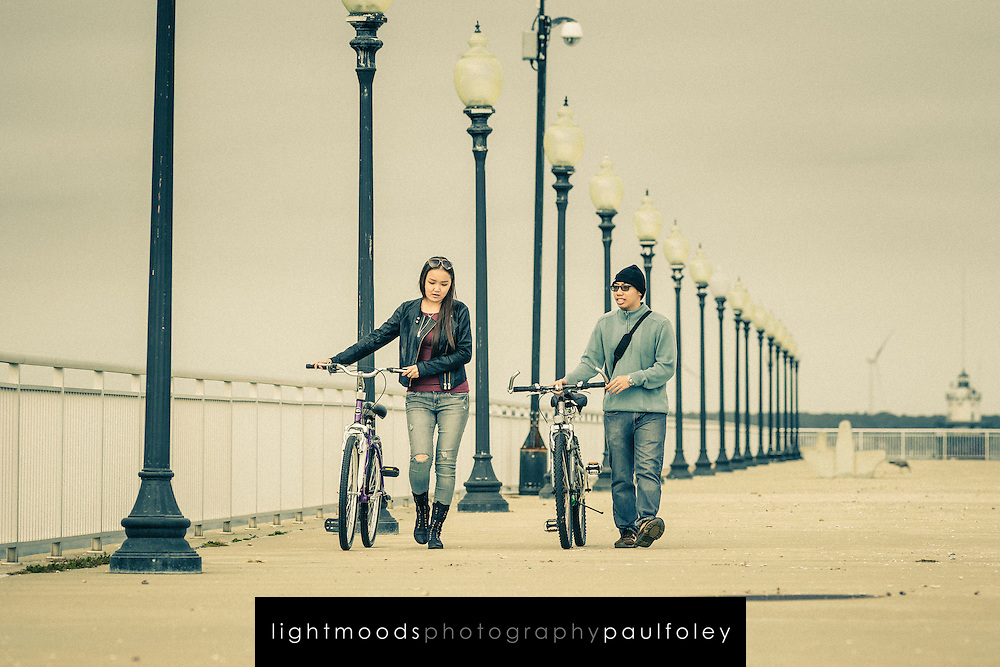 A couple walking their pushbikes along a pier in New Bedford, Massachusetts, USA