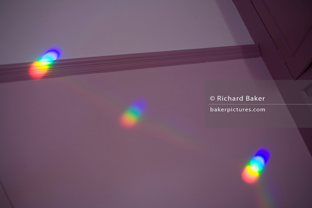 A colour (color) spectrum of visible light shines onto bedroom wall sourced from a window-situated prism.