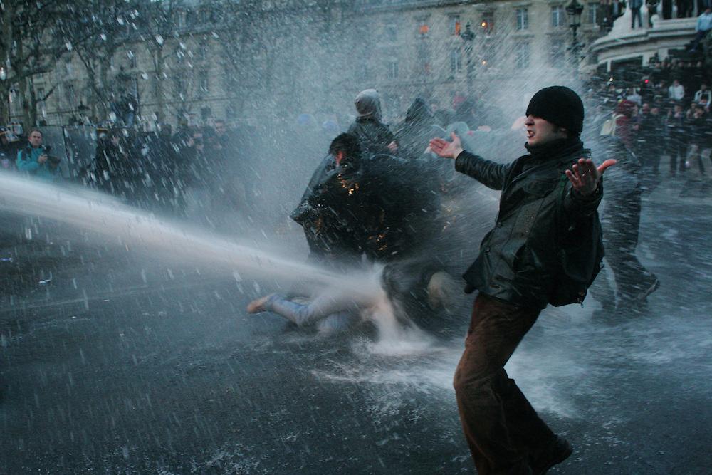 A protester evades a water canon during anti-CPE riots, Place de la Republique, Paris, France. March 2006