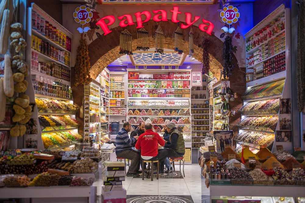 Group of men sit and gather around small table in sweet shop at Istanbul Spice bazaar in Turkey