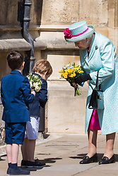 Windsor, UK. 21st April 2019. A young schoolboy bows to the Queen after presenting her with a traditional posy of flowers outside St George's Chapel in Windsor Castle following the Easter Sunday service.