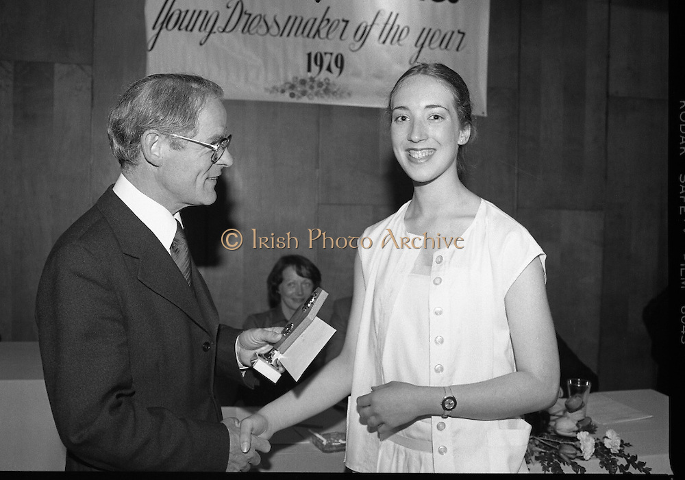Young Dress Designer of the Year.     (M75).1979..22.05.1979..05.22.1979..22nd May 1979..The Cassidy Fabrics sponsored Young Dress Designer of the Year, make and model competition was held today in Liberty Hall,Dublin. The overall winner of the competition was Ms Marianne Byrne (15),Cabinteely,Co Dublin. Ms Byrne is a pupil at the Cabinteely Community School...Image shows Mr Michael Cassidy,Director Cassidy Fabrics, presenting her group award to Ms Marianne Byrne.