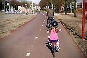 In Utrecht fietst een meisje  met een helm op achterop de bagagedrager over het fietspad tussen het centrum en de Uithof.<br /> <br /> In Utrecht a young girl cycles with a helmet on her head.