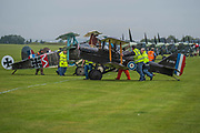 British and German World War 1 bi planes are prepared on the grass stand - Duxford Battle of Britain Air Show taking place during IWM (Imperial War Museum) Duxford's centenary year. Duxford's principle role as a Second World War fighter station is celebrated at the Battle of Britain Air Show by more than 40 historic aircraft taking to the skies.
