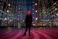 © Licensed to London News Pictures. 14/01/2019. London, UK. Martine Basson looks at 'Submergence' a light installation created by Squidsoup as part of Canary Wharf's Winter Lights 2019. Photo credit : Tom Nicholson/LNP