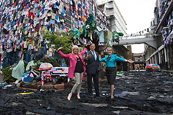 © licensed to London News Pictures. London, UK 26/04/2012. Joanna Lumley, Marc Bolland (CEO of M&S) and Barbara Stocking (CEO of Oxfam) posing in a street covered with clothes from walls, the road, and the pavement to a fabric-strewn bench, car and even a dog to illustrate future uses for old clothes in Brick Lane. M&S will be accepting people's old and unwanted clothes for their charity campaign with Oxfam. Photo credit: Tolga Akmen/LNP