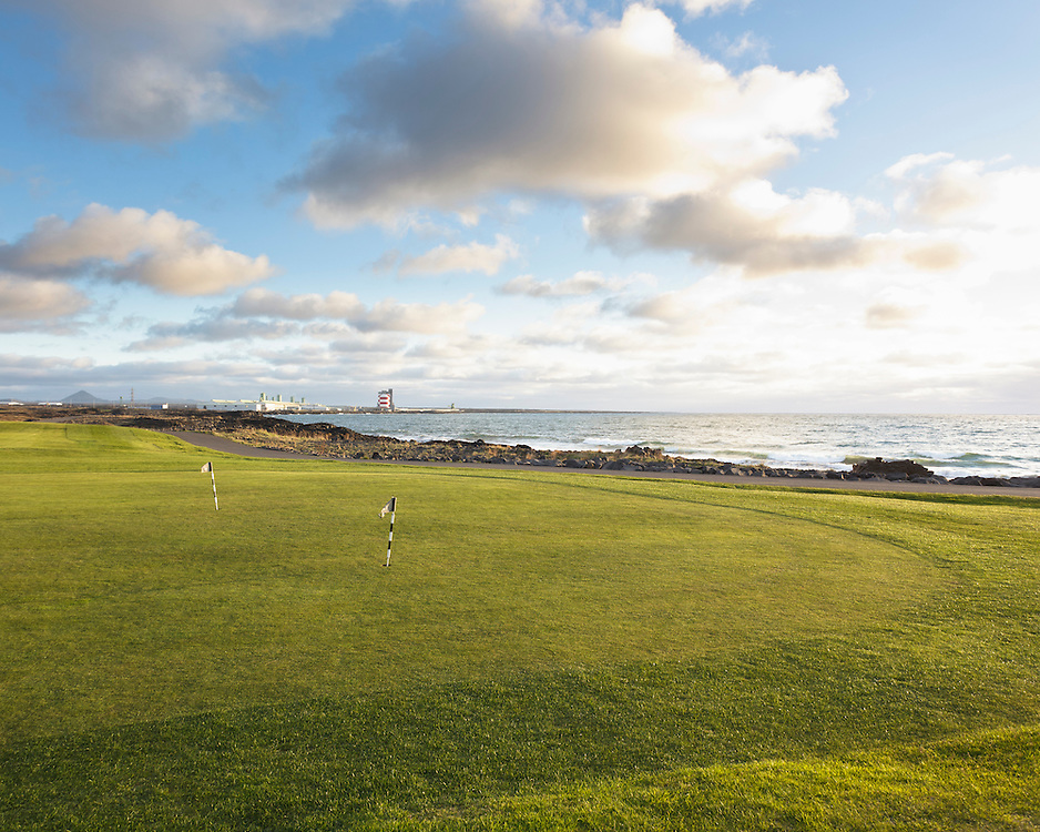 Golf course in Hafnafjordur with industrial buildings in the background
