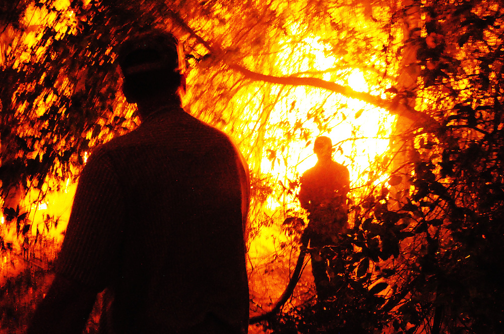 Andrew Knapp, FLORIDA TODAY -- March 1, 2011 -- Residents use a high-power water hose used for orange groves to fight flames from a massive wildfire after it crossed U.S. 1 early Tuesday morning just south of Stuckway Road in Mims.