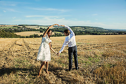Couple in Field Holding Hands Making Heart Shape