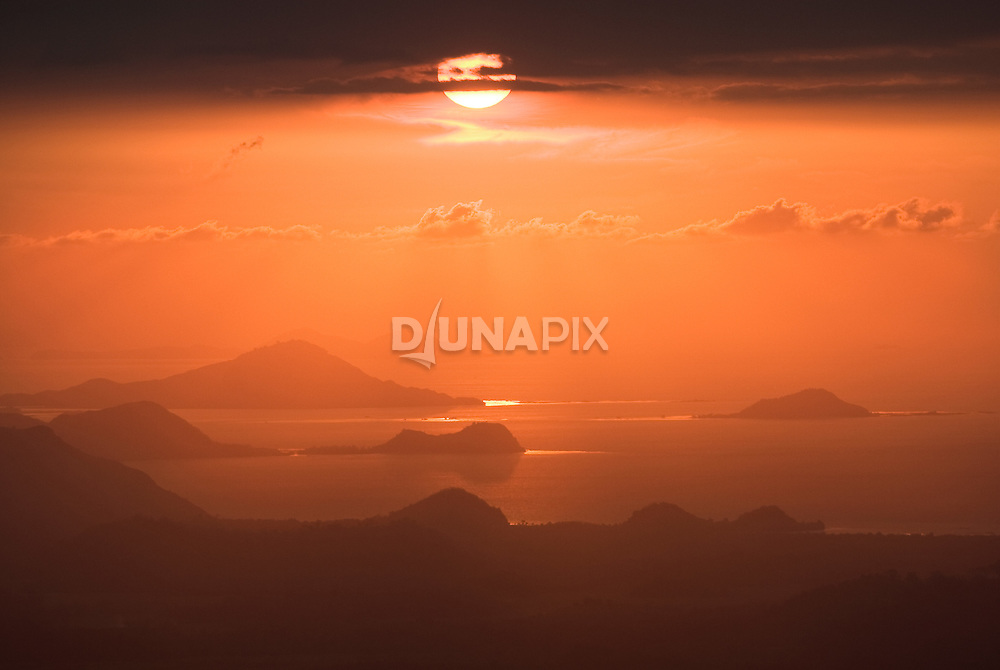View from Flores towards the islands of Komodo, under a red sunset. MIllion-year old stone tools in Flores suggest that mankind's first-ever maritime voyage may have made landfall not far from here.