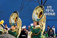 """MANHATTAN - MARCH 17: St. Patrick's Day Parade reflected on Tubas of High School Band marches up 5th Avenue, at E. 47th Street, NYC, on March 17, 2009. """"575 FIFTH AVENUE"""" painted on blue construction wall in background. (glimpse of hat of someone in crowd in lower corner)  NOTE: Focus on reflections on tubas. Slight motion blur in marchers."""