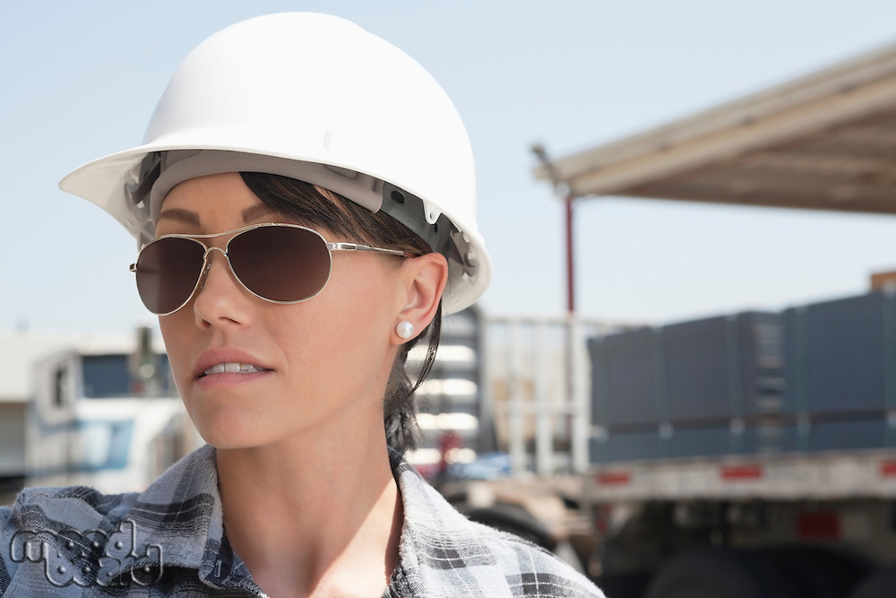 Close-up view of female industrial worker wearing hardhat and sunglasses