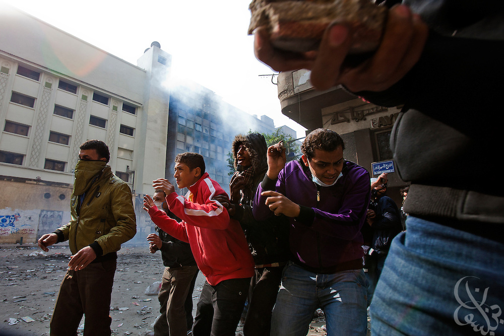 Egyptian protesters taunt nearby security forces from an alleyway refuge during continuing clashes November 22, 2011 near Tahrir square in central Cairo, Egypt. Thousands of protestors demanding the military cede power to a civilian government authority clashed with Egyptian security forces for a fourth straight day in Cairo, with hundreds injured and at least 29 protestors killed.  (Photo by Scott Nelson)