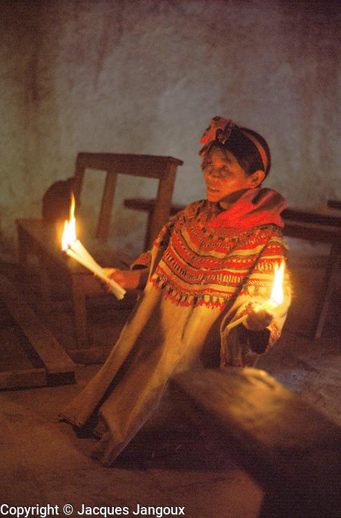 Indian woman praying holding candles in church of San Mateo Ixtatan, Cuchumatanes Mountains, Guatemala