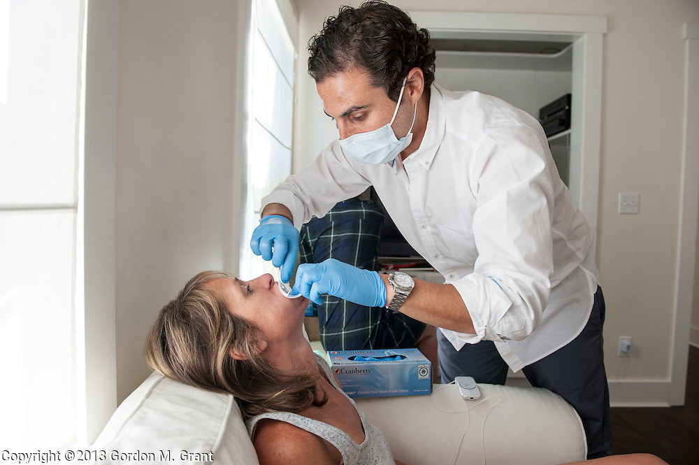 East Hampton, NY - 7/27/13 - Dr. Jeffrey Rappaport whitens the teeth of patient Kathryn Alisbah at her home in East Hampton, NY July 27, 2013. CREDIT: Gordon M. Grant for The Wall Street Journal<br /> NYTEETH