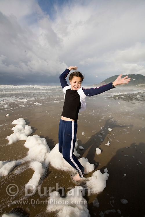 Nine year old Isabel Durham plays in sea foam on the beach at the Oregon Coast. (Fully released - 111106)