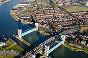 Nederland, Zuid-Holland, Krimpen aan den IJssel, 18-02-2015; stormvloedkering in de Hollandsche IJssel. Bij storm en dreigend hoog water wordt een van de twee schuiven naar beneden gelaten, de tweede schuif dient al reserve. De scheepvaart kan de gesloten kering paseren via de naastgelegen schutsluis. De stormvloedkering maakt deel uit van de Deltawerken en is als eerste voltooid in 1958. Ten tijde van De Ramp - watersnood 1953 - werd het zeewater door de storm opgestuwd en dreigde de verzwakte rivierdijken in het achterland het te begeven waardoor grote van het laag gelegen westen van Nederland ondergelopen zouden zijn. Krimpen at the river IJssel, near Rotterdam: storm surge barrier, protects the highly populated western part of Holland, which lies below sea level. In case of storm and threat of high water, one of the two doors is lowered into the river (the second door is a spare one). The lock next to the barrier allows shipping when the barrier is closed. luchtfoto (toeslag op standard tarieven);<br /> aerial photo (additional fee required); copyright foto/photo Siebe Swart