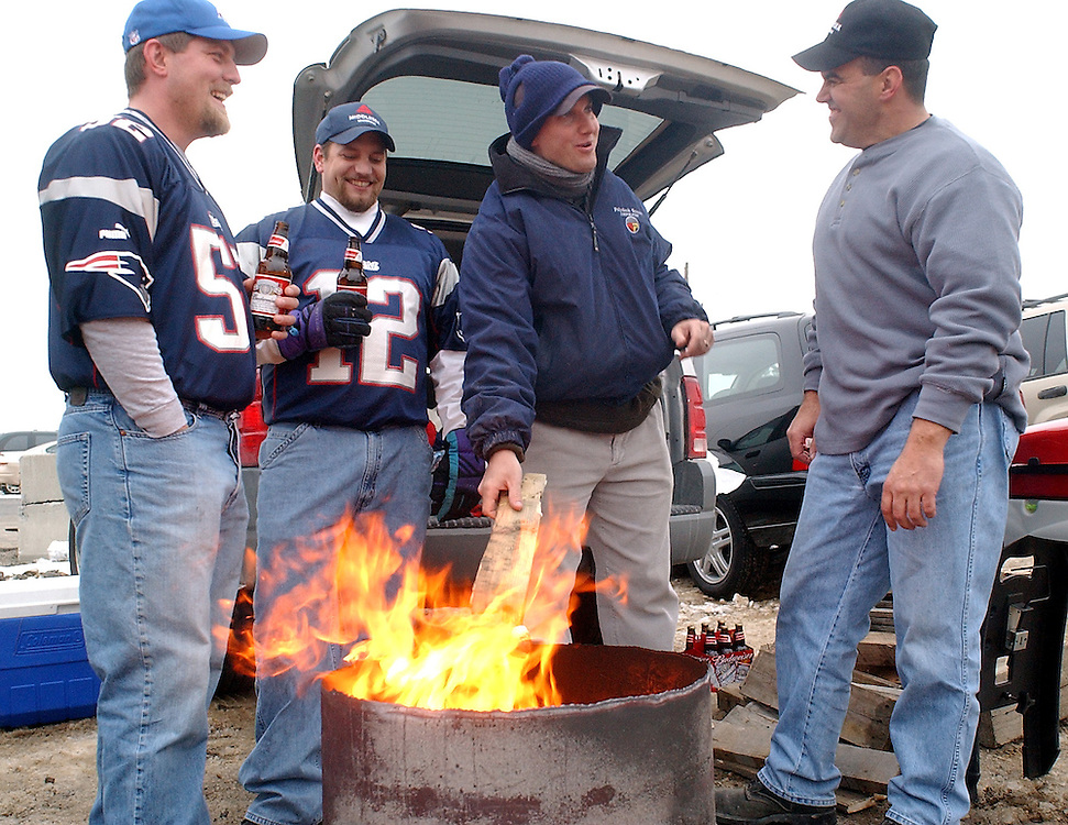(1/19/02 Foxboro, MA) Patriots vs. Raiders at Foxboro Stadium. (l-R) Dave Scofield, Chad Abramson, Mark Landry, and Mark Lovallo stoke up the fire to keep warm as they get ready for the game. (011902patsmjs.JPG- Staff Photo by Michael Seamans. Saved in Sunday/FTP)